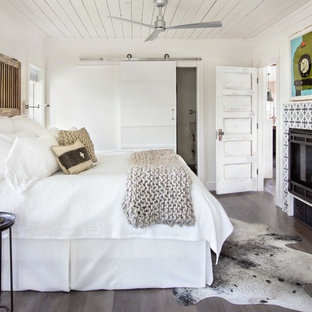 Example of a cottage dark wood floor and brown floor bedroom design in Other with white walls, a tile fireplace and a ribbon fireplace