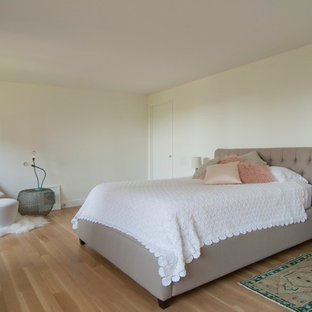 Example of a large trendy master light wood floor and beige floor bedroom design in New York with no fireplace