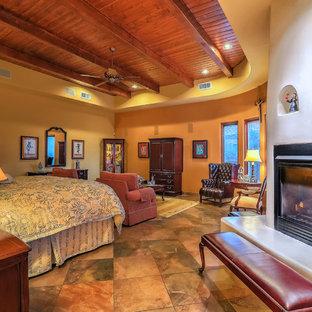 Пример оригинального дизайна: огромная хозяйская спальня с бежевыми стенами, полом из травертина, стандартным камином, фасадом камина из штукатурки и бежевым полом