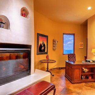 Идея дизайна: хозяйская спальня среднего размера в стиле фьюжн с желтыми стенами, полом из сланца, стандартным камином, фасадом камина из штукатурки и разноцветным полом