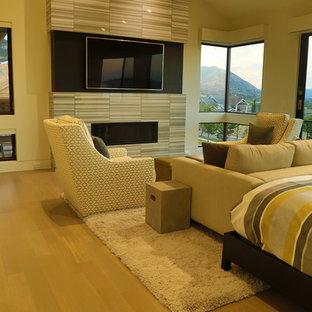 Modelo de dormitorio principal, clásico renovado, grande, con paredes beige, suelo de madera clara, chimenea lineal y marco de chimenea de baldosas y/o azulejos