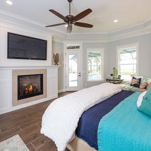 Foto de dormitorio principal, marinero, grande, con paredes grises, suelo de baldosas de porcelana, chimenea tradicional y marco de chimenea de piedra
