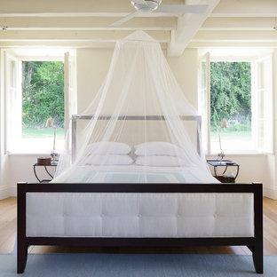 Idée de décoration pour une chambre tradition avec un mur beige, un sol en bois clair et aucune cheminée.