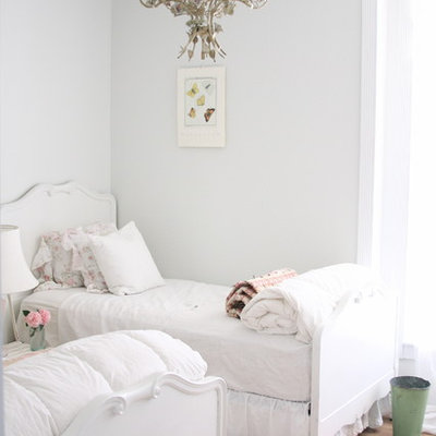 Inspiration for a shabby-chic style guest light wood floor bedroom remodel in Other with white walls