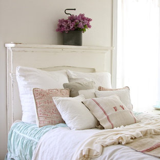 Shabby chic-inspirerad inredning av ett sovrum, med vita väggar