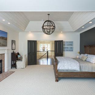 Foto de dormitorio principal, tradicional, grande, con paredes blancas, moqueta, chimenea tradicional, marco de chimenea de ladrillo y suelo gris