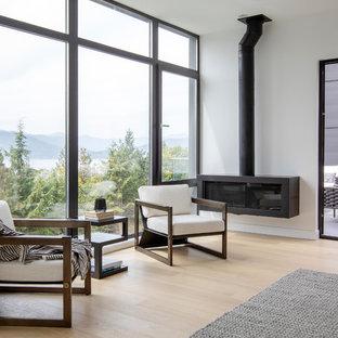 バンクーバーの大きいモダンスタイルのおしゃれな主寝室 (白い壁、淡色無垢フローリング、吊り下げ式暖炉、金属の暖炉まわり、ベージュの床) のインテリア