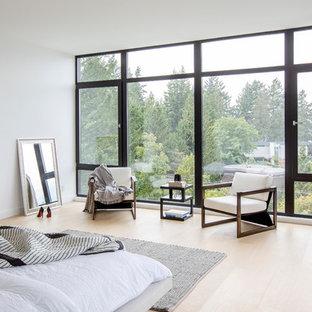 Diseño de dormitorio principal, moderno, grande, con paredes blancas, suelo de madera clara, chimeneas suspendidas, marco de chimenea de metal y suelo beige