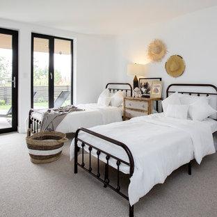 Foto de habitación de invitados moderna, grande, con paredes blancas, moqueta, chimeneas suspendidas, marco de chimenea de metal y suelo gris