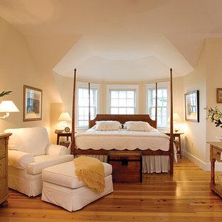 Ejemplo de dormitorio principal, tradicional, extra grande, con paredes amarillas y suelo de madera en tonos medios