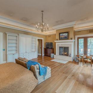 Идея дизайна: огромная хозяйская спальня в классическом стиле с коричневыми стенами, паркетным полом среднего тона, стандартным камином, фасадом камина из плитки и коричневым полом