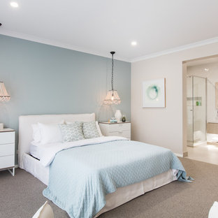 This is an example of a mid-sized beach style bedroom in Other with carpet, brown floor and blue walls.