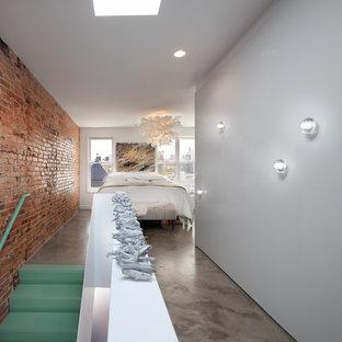 Industriell inredning av ett mellanstort huvudsovrum, med vita väggar och betonggolv