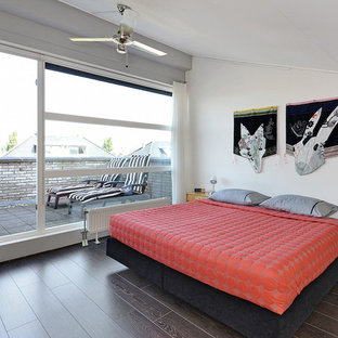 Example of a mid-sized trendy loft-style plywood floor bedroom design in Amsterdam with beige walls