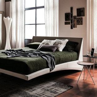 Modelo de dormitorio principal, bohemio, grande, con paredes beige, suelo de baldosas de terracota y suelo rojo