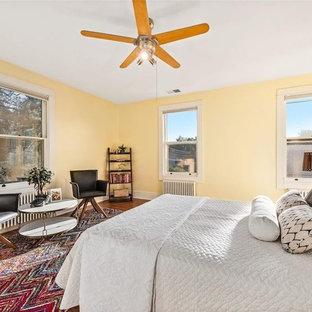 デンバーの中くらいのミッドセンチュリースタイルのおしゃれな客用寝室 (黄色い壁、無垢フローリング、暖炉なし、茶色い床)