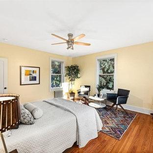 デンバーの中くらいのミッドセンチュリースタイルのおしゃれな客用寝室 (黄色い壁、無垢フローリング、暖炉なし、茶色い床) のインテリア