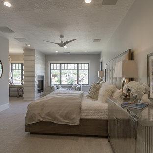 Idéer för stora funkis huvudsovrum, med vita väggar, heltäckningsmatta, en dubbelsidig öppen spis och en spiselkrans i trä