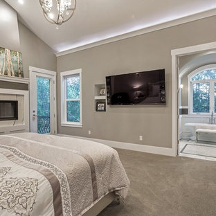 Bild på ett stort amerikanskt gästrum, med grå väggar, heltäckningsmatta, en bred öppen spis, en spiselkrans i trä och grått golv