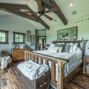 Ejemplo de dormitorio principal, rústico, de tamaño medio, con paredes azules, suelo de madera oscura y suelo multicolor