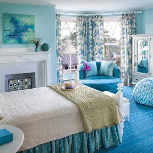 Ejemplo de dormitorio principal, marinero, de tamaño medio, con paredes azules, moqueta, suelo azul, chimenea tradicional y marco de chimenea de madera