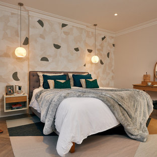 Medium sized contemporary master bedroom in London with medium hardwood flooring, white walls and no fireplace.