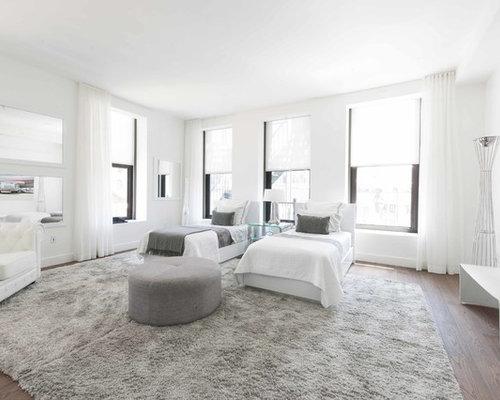 Example Of A Trendy Dark Wood Floor Bedroom Design In New York With White Walls