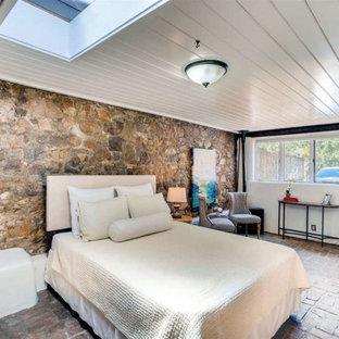 アルバカーキのサンタフェスタイルのおしゃれな寝室 (白い壁、レンガの床、コーナー設置型暖炉、赤い床)