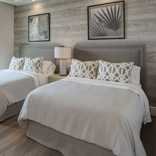 Example of a mid-sized coastal guest medium tone wood floor and gray floor bedroom design in Cleveland with no fireplace and gray walls