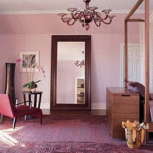 Modelo de dormitorio principal, actual, de tamaño medio, sin chimenea, con paredes púrpuras y suelo de madera en tonos medios