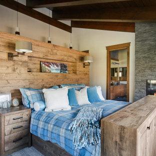 Aménagement d'une chambre parentale montagne de taille moyenne avec un manteau de cheminée en pierre de parement, un plafond en poutres apparentes, un plafond voûté, un plafond en bois, un mur blanc, un sol en bois brun, une cheminée ribbon et un sol marron.