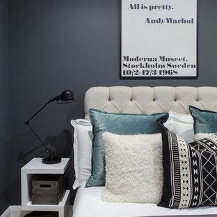 Example of a trendy light wood floor bedroom design in London with black walls