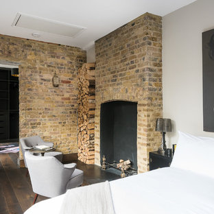 Inspiration for an eclectic master dark wood floor bedroom remodel in London with a standard fireplace and a brick fireplace