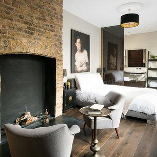 Inredning av ett medelhavsstil huvudsovrum, med mörkt trägolv, en standard öppen spis, en spiselkrans i tegelsten, beige väggar och brunt golv