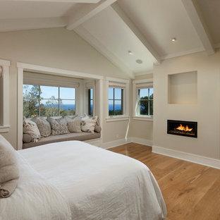 Idées déco pour une grand chambre parentale classique avec une cheminée ribbon, un mur beige, un sol en bois brun et un manteau de cheminée en plâtre.