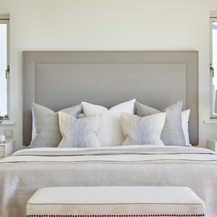 This is an example of a beach style master bedroom in London with white walls, light hardwood flooring and no fireplace.