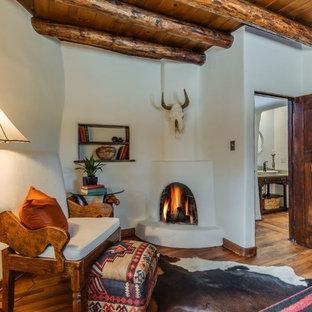 アルバカーキの中サイズのサンタフェスタイルのおしゃれな主寝室 (ベージュの壁、無垢フローリング、漆喰の暖炉まわり、コーナー設置型暖炉、茶色い床) のレイアウト