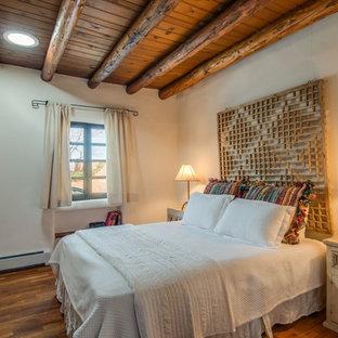 アルバカーキの小さいサンタフェスタイルのおしゃれな主寝室 (ベージュの壁、無垢フローリング、暖炉なし、茶色い床) のレイアウト