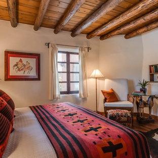 アルバカーキの中くらいのサンタフェスタイルのおしゃれな主寝室 (ベージュの壁、無垢フローリング、漆喰の暖炉まわり、コーナー設置型暖炉)