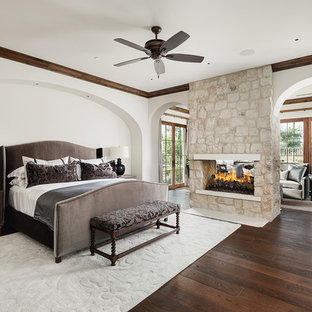 Photo of a mid-sized mediterranean master bedroom in Phoenix with white walls, dark hardwood floors, a two-sided fireplace, a stone fireplace surround and brown floor.