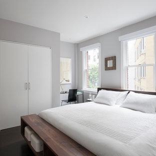 Exemple d'une chambre parentale moderne de taille moyenne avec un mur gris, un sol en bois foncé, aucune cheminée et un sol marron.