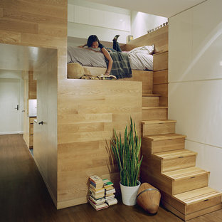 Photo of a contemporary mezzanine bedroom in New York with white walls and dark hardwood flooring.