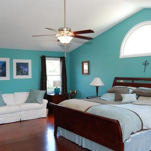 Foto di una camera matrimoniale classica di medie dimensioni con pareti blu e pavimento in compensato