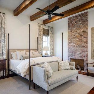 Example of a large classic master medium tone wood floor, red floor and exposed beam bedroom design in New Orleans with white walls, a standard fireplace and a brick fireplace