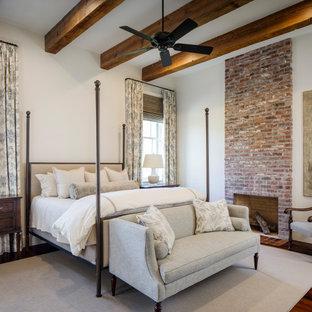 ニューオリンズの広いトラディショナルスタイルのおしゃれな主寝室 (白い壁、無垢フローリング、標準型暖炉、レンガの暖炉まわり、赤い床、表し梁)