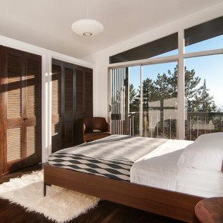 Example of a trendy dark wood floor bedroom design in Salt Lake City with white walls
