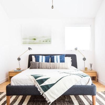 Danish master light wood floor and brown floor bedroom photo in Los Angeles with white walls