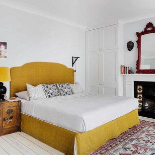 Modelo de dormitorio principal, bohemio, con paredes grises, suelo de madera clara y chimenea tradicional