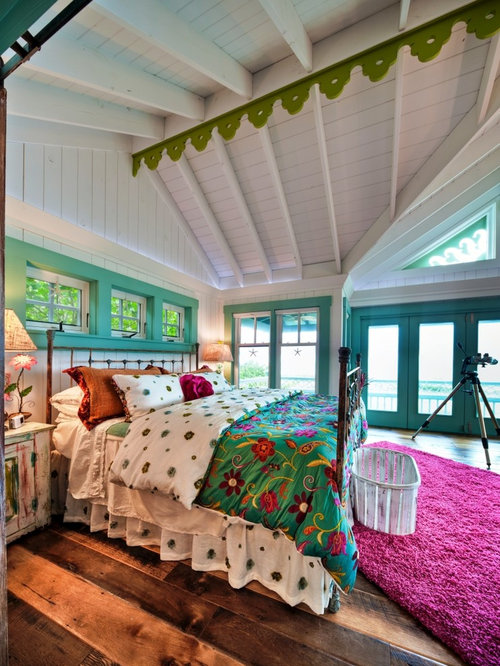 Example Of An Eclectic Medium Tone Wood Floor Bedroom Design In Tampa With White Walls