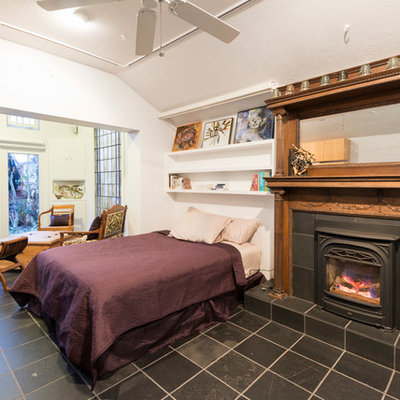 Example of a large eclectic master bedroom design in San Francisco with white walls and a standard fireplace